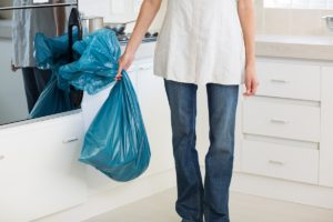 Woman carrying a garbage bag in the kitchen