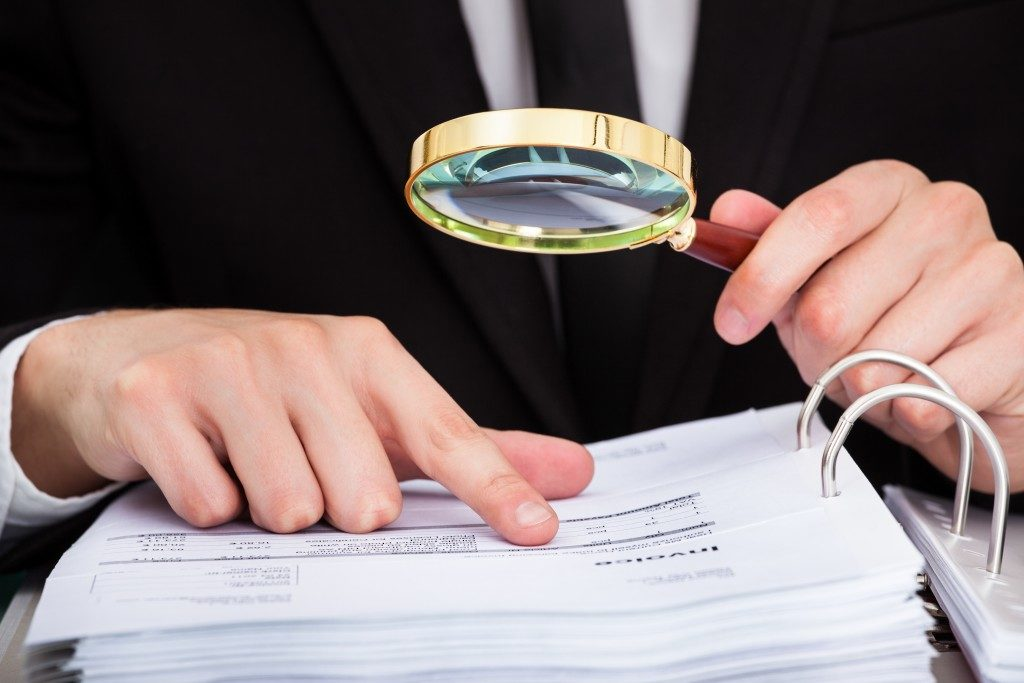 person in suit looking at a document through magnifying glass