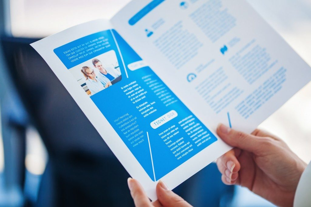 Hands holding a print of a business bi-fold brochure
