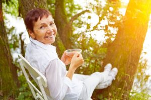 grandmother relaxing beside trees and drinking tea