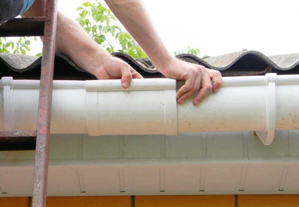 man installing a vinyl gutter