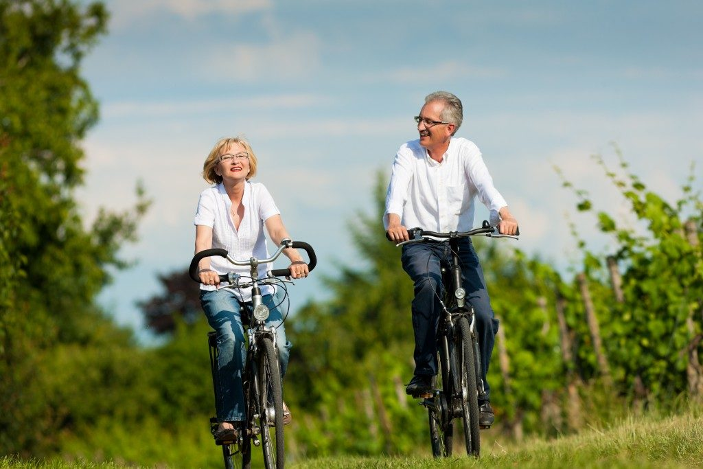 two senior couple riding bikes by the forest