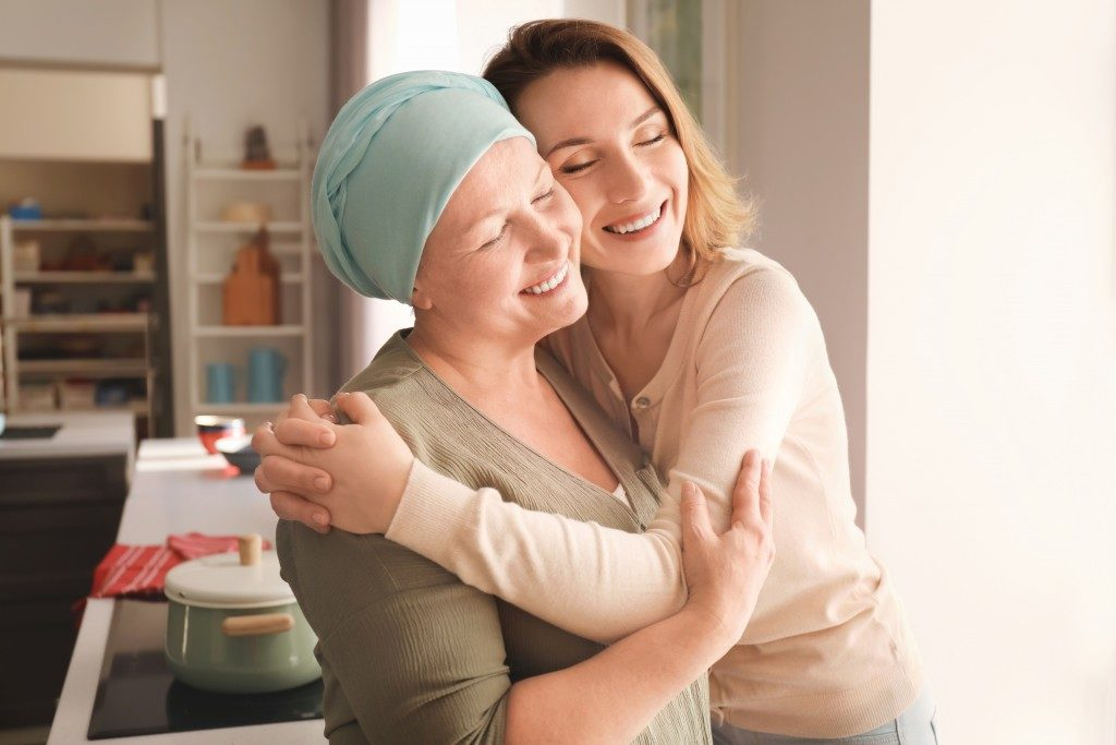 Woman with cancer hugging her daughter