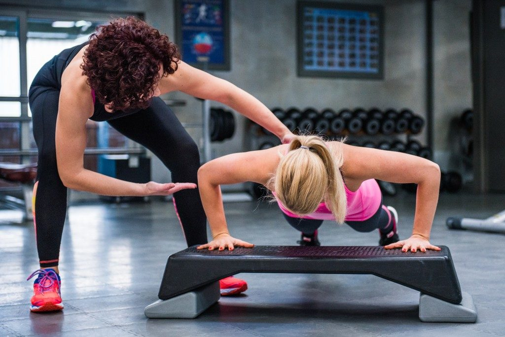 coach training her client in the gym