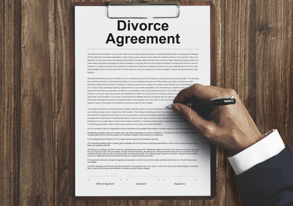 man signing on a divorce agreement document