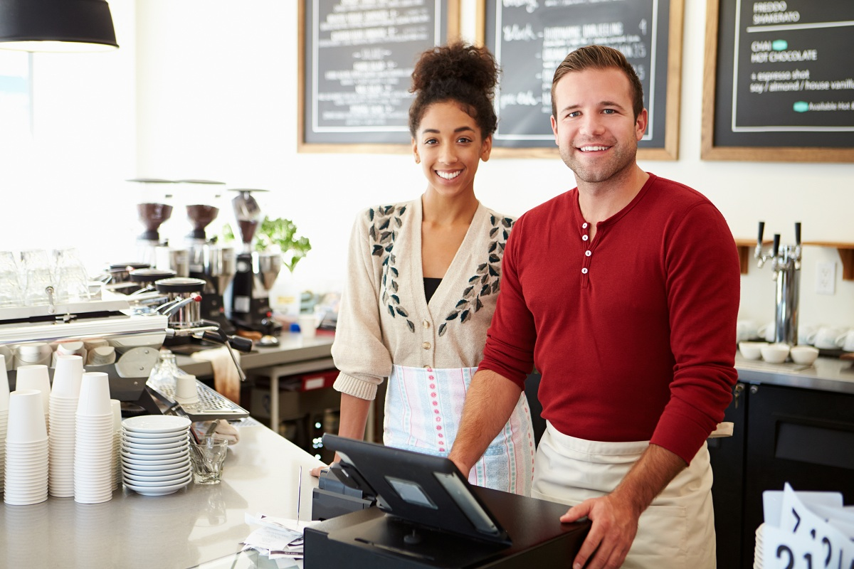 man and woman standing behind the counter