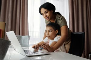 woman helping child with online classes