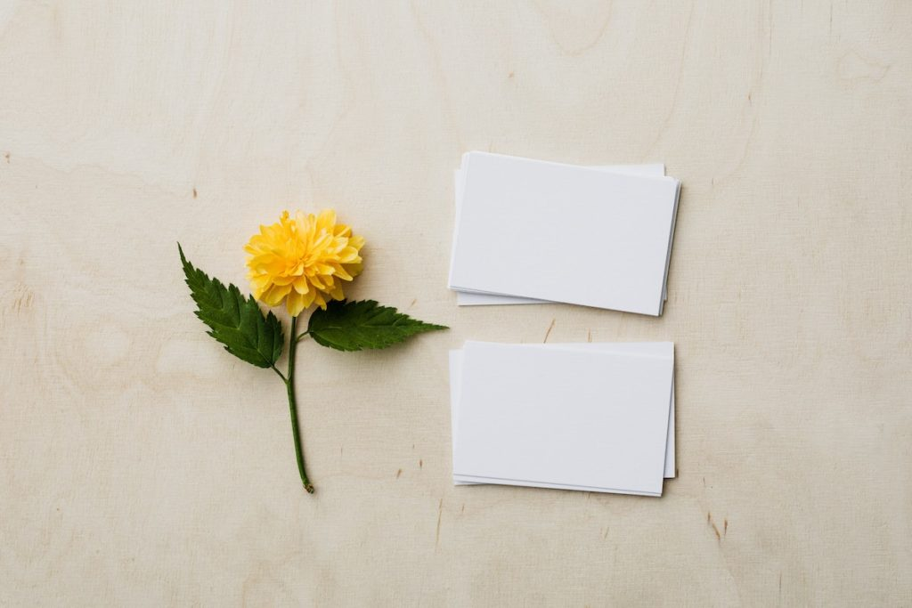 yellow flower next to white business cards