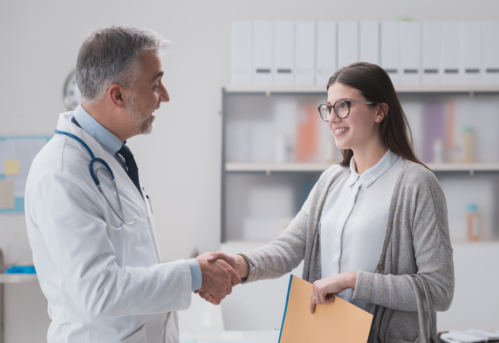 doctor and woman shaking hands